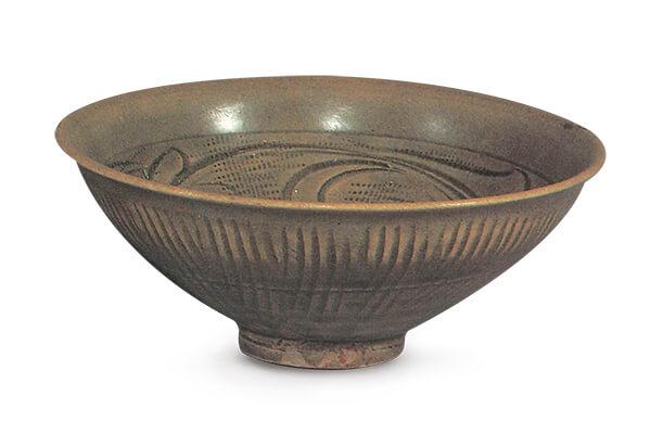(图五)+宋代.同安窑青瓷碗+此器以大斜刀和篦纹作装饰,因积釉多寡而有深浅之分,纹饰风格流畅。图片来源:《金明集瓷选录》,页91。